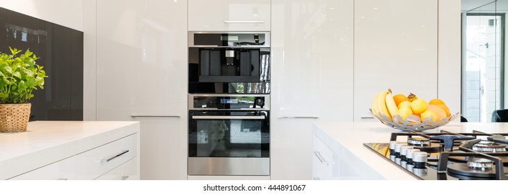 Very bright and high-polished kitchen with white furniture unit and built in oven and coffee maker