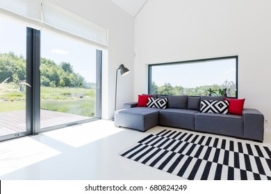 Very bright living room in a modern house, with a large corner sofa and panoramic windows overlooking picturesque neighbourhood