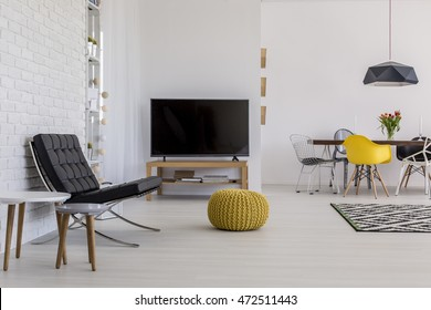 Very bright modern living room with white brick wall, panelled flooring and a tv cabinet