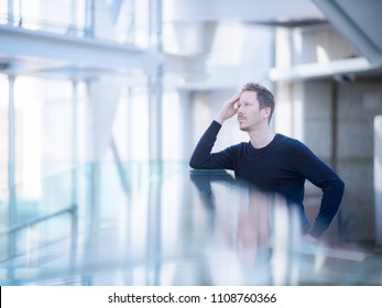 In a very bright room, like a large office or an ariport terminal, a thoughtful man stands, strong reflection effect with glass.