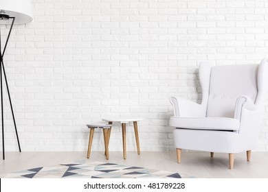 Very bright shot of white wing chair, set of coffee tables and a floor lamp next to a white brick wall