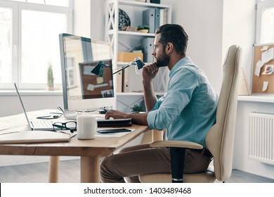 Very busy. Young modern businessman analyzing data using computer while sitting in the office