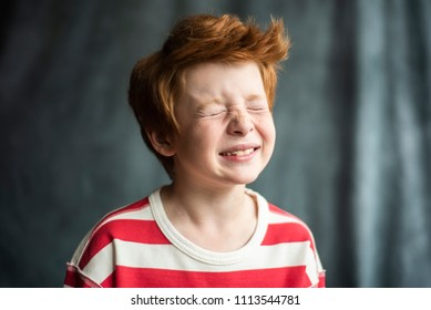 Very charismatic handsome funny red boy portrait in the studio. Red hair cute kids. Handsome children. Boy is laughing. Stripe clothes. Kids actors.