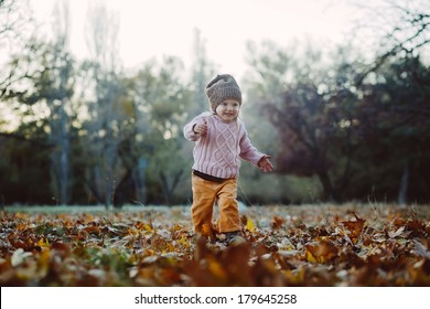 Very cheerful child having fun while tossing up leaves