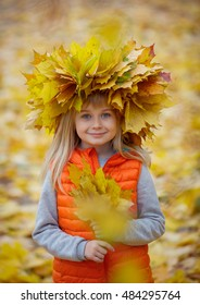 Very cheerful girl having fun with yellow leaves in autumn park