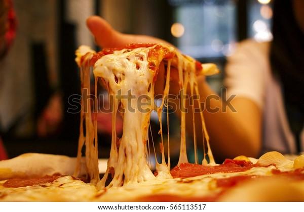 Muito queijo fatia de pizza na mão.Pizza é um prato salgado de origem italiana, consistindo de uma base geralmente redonda, achatada de massa à base de trigo fermentada coberto.