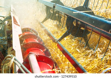 very close up combine harvesting wheat