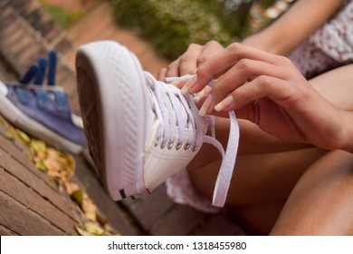Very close up shot of a girl tying her white sneakers, while sitting on the stairs of a park