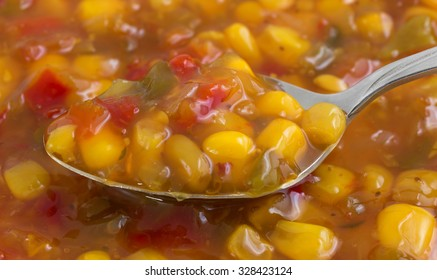 A very close view of corn relish on a spoon illuminated with natural light.