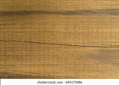 A very close view of a cracked pressure treated wood beam.