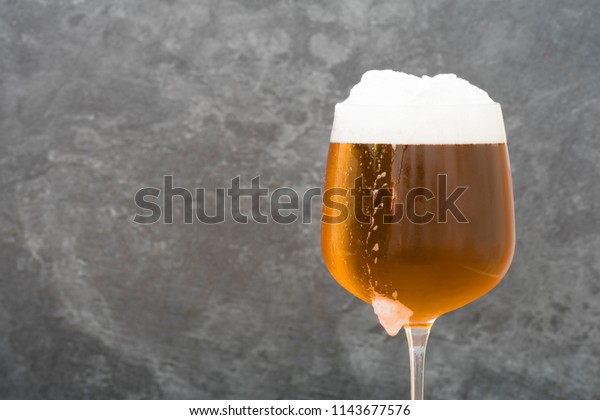 Very cold beer glass on a gray background