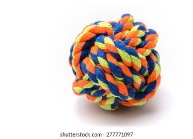 A very colorful ball made from rope tied in a monkey's fist knot used for a dog's toy.