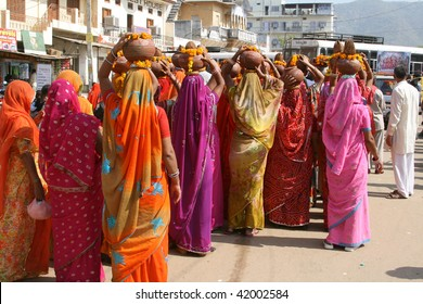 Very colorful ladies with pots on their heads