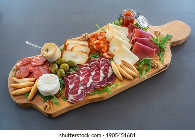 Very colorful tapas board of charcuterie with cheese and smoked meats. Decorated with arugula and walnuts.