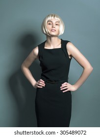 very confident Beautiful young blonde woman in a strict black dress in the studio with short hair and threw her head up holding hands on hips