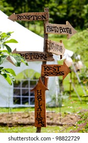 A very cool and unique wedding sign showing guests directions to various areas and a tent in the background.