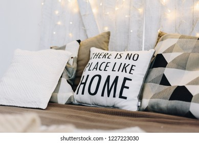 "Very cozy and modern Christmas interior design idea with pillows and Christmas lights. Words on a pillow say ""There is no place like home""."