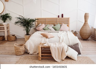 Very cozy wooden bed with a bedspread of pastel colors, pillows of powdery shades and a blanket of delicate colors. Stylish bedroom in the style Boho.