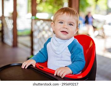 Very cute beautiful baby boy sitting in the highchair black