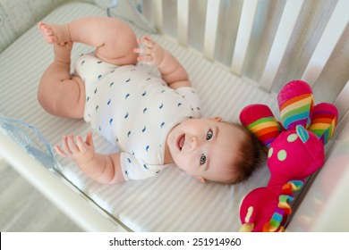 Very cute little baby boy lying on the bed at the back in the crib next to a bright toy