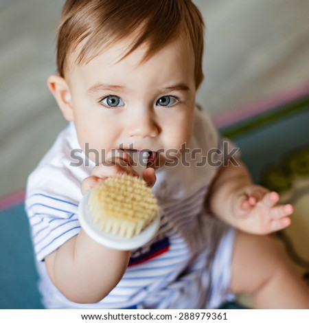 Very cute little blond boy chews on the brush for the hair, scratching his teeth, sitting on the colored carpet