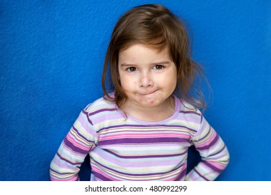 A very cute little girl with Chicken Pox looks at the camera with a mischievous look as if she is plotting something.