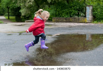 Very cute little girl in red Jacket, blue jeans and rubber boots is jumping over a puddle on a rainy day