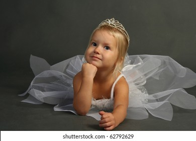Very cute thinking 3 years old ballerina girl in  white dress