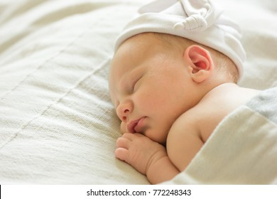 Very cute Two weeks smiling newborn baby boy . Sweet baby portrait sleeping in his bed.