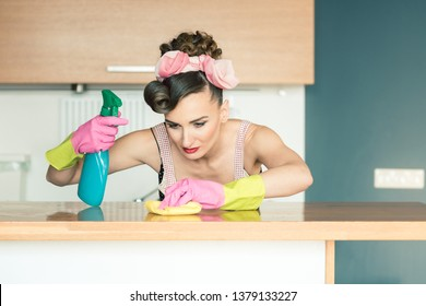 Very diligent homemaker woman cleaning the home with cloth and household cleaner