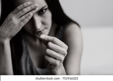 Very disappointed and offended wife depressed after divorce, holding with hand a wedding ring sitting on a room floor. Black and white toning