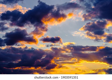 A very dramatic sky full of yellows, blues and oranges. Contrasting clouds during sunset illuminated by the setting sun. Bright saturated natural background. High quality photo