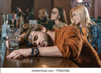 very drunk young man at bar with friends