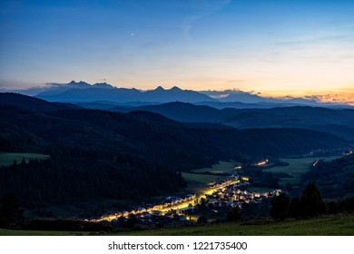 Very early morning shot of small village in front of high mountain range. Scenic view of settlement in High Tatras mountains, Slovakia.