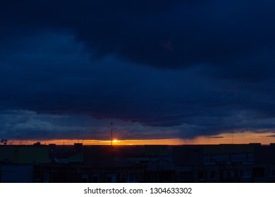 very early morning sun is rising over the horizon over the buildings sun is under the huge dark clouds
