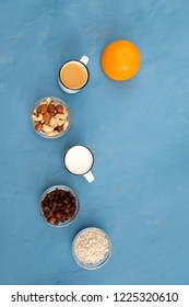 Very easy, light and wholesome breakfast for a healthy lifestyle: fresh milk, an orange juice, nuts, raisins, oat flakes. Blue background.