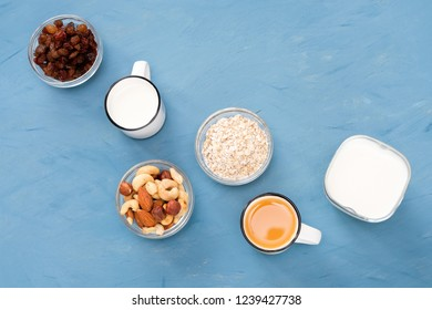 Very easy, light and wholesome breakfast for a healthy lifestyle: fresh milk, an orange juice, nuts, raisins, oat flakes, yoghurt. Blue background.