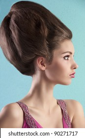very elegant young pretty wearing a pink dress and creative hair style over turquoise background