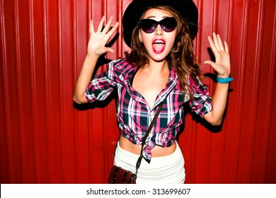 Very emotional portrait of Fashion stylish portrait of pretty young hipster blonde woman,going crazy,elegant black hat,soft colors,cool crazy teen girl.Red urban wall background.surprised girl