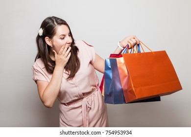 Very escited enthusiastic girl screams standing with shopping bags
