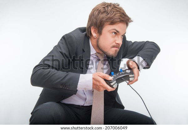 Very excited handsome businessman in perfect black suit making great efforts to win a video game