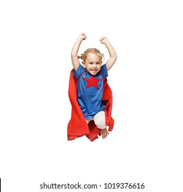 Very excited little girl dressed like hero jumping isolated on white background.