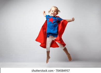 Very excited little girl dressed like superhero jumping alongside the white wall.