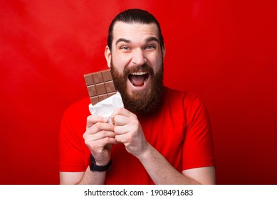 A very excited man is eating a chocolate in front of camera looking at it .