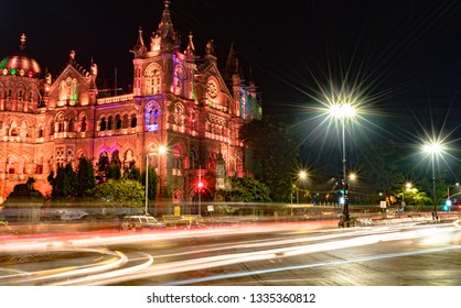 Very famous Victoria Terminus of Mumbai,aka Chhatrapati Shivaji Maharaj Terminus, during night with fast moving traffic trails and street light glares. A UNESCO World Heritage and a local Rly. Station
