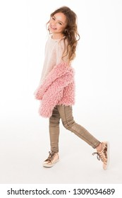 Very fashionable child posing in the studio. Gold metallic shoes, pink fur coat, blouse and jeans with glitter.