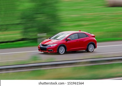 Very fast driving red Japanese modern hatchback