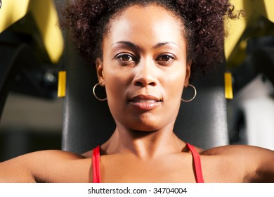 Very fit and beautiful african-american woman in a gym working out and lifting weights on an exercising machine