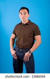 Very fit and relaxed young Asian man in casual shirt and denim trousers.