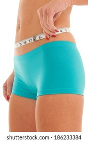 Very fit young woman wraps white measuring tape around her waist. She is wearing blue women's sport shorts.
